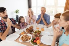Family praying for a holiday table for Thanksgiving, holding folded hands in front of you. The family gathered at a festive table, on which there are dishes for royalty free stock photo
