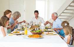 Family praying together before meal at dining table Royalty Free Stock Photography