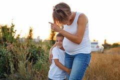 Family. Pregnant mother and son. Family values. Pregnant mother and son are walking in the field at sunset. She shows the boy somewhere, and the son hugs her leg Royalty Free Stock Photo