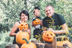 Family preparation for Halloween in the garden near Jack-o-Lantern decorations. Happy. Father, mother and daughter with pumpkins . Stock Photos