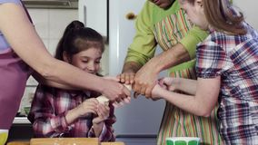 Family prepares delicious meal and stretches thick dough. Roll above cooking table with equipment laughing closeup stock footage