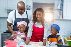 Family preparing cake. In kitchen Stock Images