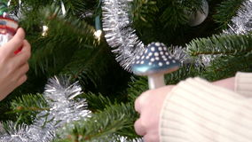 Family preparing for Christmas - Hands decorating a pine tree. - 4 k stock video footage