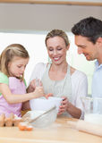 Family preparing cookies together. Smiling family preparing cookies together royalty free stock images