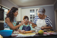 Family preparing dessert in kitchen Royalty Free Stock Images