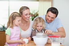 Family preparing dough. Smiling family preparing dough together royalty free stock image