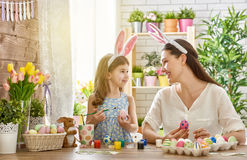 Family preparing for Easter. Happy easter! A mother and her daughter painting Easter eggs. Happy family preparing for Easter. Cute little child girl wearing royalty free stock photo