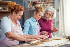 Happy family of three generations preparing gingerbread cookies rolling royalty free stock image