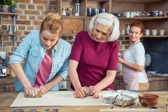 Family of three generations preparing gingerbread cookies stock photography