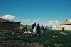 family preparing grain for the chicken next to their yurt high up in the mountains of Alai Range royalty free stock images