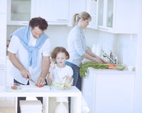 Family preparing healthy meal in kitchen Stock Images