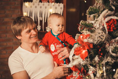 Family preparing home for xmas celebration. Father with his Little son decorating christmas tree with toys and flowers. Family preparing home for xmas royalty free stock photo