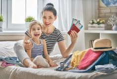 Family preparing for the journey. Go on an adventure! Happy family preparing for the journey. Mom and daughter are packing suitcases for the trip Stock Images