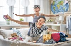 Family preparing for the journey. Go on an adventure! Happy family preparing for the journey. Mom and daughter are packing suitcases for the trip Royalty Free Stock Image
