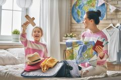 Family preparing for the journey. Go on an adventure! Happy family preparing for the journey. Mom and daughter are packing suitcases for the trip Royalty Free Stock Photos