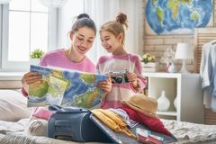 Family preparing for the journey. Go on an adventure! Happy family preparing for the journey. Mom and daughter are packing suitcases for the trip Stock Image