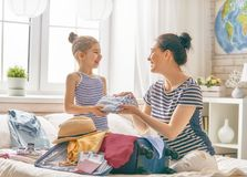 Family preparing for the journey. Go on an adventure! Happy family preparing for the journey. Mom and daughter are packing suitcases for the trip Stock Photography
