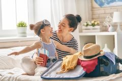 Family preparing for the journey. Go on an adventure! Happy family preparing for the journey. Mom and daughter are packing suitcases for the trip Royalty Free Stock Photo