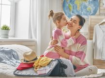 Family preparing for the journey. Go on an adventure! Happy family preparing for the journey. Mom and daughter are packing suitcases for the trip Royalty Free Stock Images