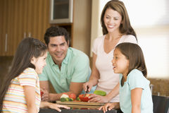 Family Preparing A Meal Together. In Kitchen Smiling stock image