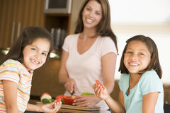 Family Preparing Meal Together. Girls Eating Pepper Strips While Mother Is Preparing meal royalty free stock photos