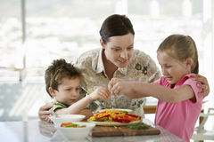 Family Preparing Meal Together In Kitchen Stock Image