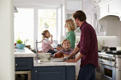 Family Preparing Roast Turkey Meal In Kitchen Together Stock Images