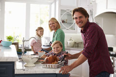 Family Preparing Roast Turkey Meal In Kitchen Together Stock Image