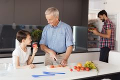 The family is preparing a salad for Thanksgiving. The old man cuts vegetables, the boy eats an apple Royalty Free Stock Photography