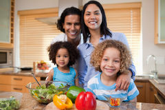 Family preparing salad together Royalty Free Stock Photos