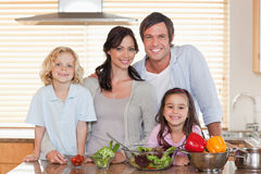 Family preparing a salad together Royalty Free Stock Photography