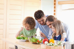 Family preparing a salad together Stock Photo