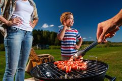 Family preparing sausages on a grill Royalty Free Stock Photo