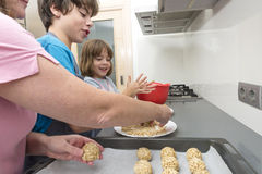 Family preparing sweets in the kitchen Stock Images