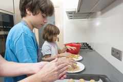 Family preparing sweets in the kitchen Stock Image