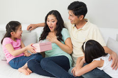 Family presenting surprised mother with a gift box in living room Royalty Free Stock Photos