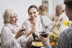 Family is a priceless treasure... Grandparents, granddaughter and young married couple sitting beside table during dinner Royalty Free Stock Photos