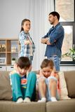 Sad children and parents quarreling at home. Family problem, conflict and people concept - sad children closing ears while their parents quarreling at home royalty free stock photo