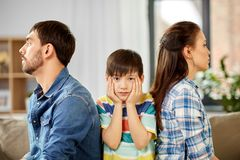 Unhappy family at home. Family problem, divorce and people concept - unhappy father, mother and sad little son at home royalty free stock photo