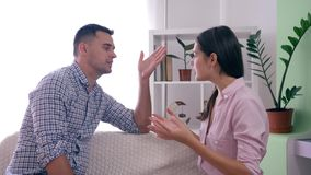 Family problems, Aggressive wife quarrels with husband and furious gestures hands during dispute in room