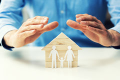 Family property, life and health insurance concept. Man protecting house model stock photos