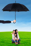 Family protection concept. Photo of joyful asian family sitting on the grass at field under umbrella. Family protection concept Royalty Free Stock Photo