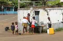 Family on public water pump, Santana, Sao Tome Royalty Free Stock Image