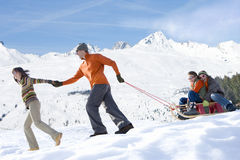 Family pulling sled in the snow Royalty Free Stock Photo