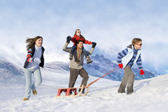 Family pulling sled in snow Stock Photos