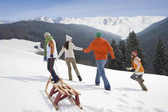 Family pulling sled up mountain top ski slope Stock Photos