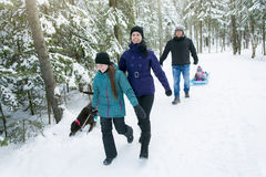 Family Pulling Sledge Through Snowy Landscape Royalty Free Stock Image