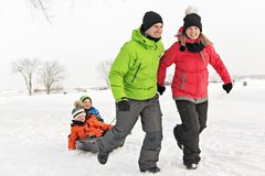 Cute Family Pulling Sledge Through Snowy Landscape royalty free stock image