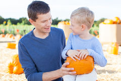 Family at pumpkin patch. Cheerful little boy and his young father holding pumpkin enjoying halloween time at pumpkin patch Royalty Free Stock Image