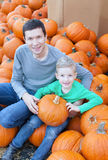 Family at pumpkin patch. Cheerful little boy and his young father holding pumpkin enjoying halloween time at pumpkin patch Royalty Free Stock Photography